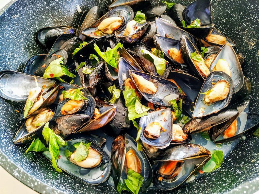 Antipasti economici a base di pesce: cozze aperte alla vampa con vino bianco olio evo e basilico!