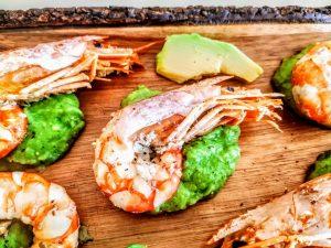 Secondi piatti a base di pesce: gamberoni al vino bianco su crema di zucchine e avocado