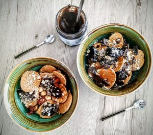 Dolci senza burro e senza lattosio: cereali pancakes di farina di miglio bruno e acqua di cocco con bacche di Goji prugne secche e crema di castagne ceci e cacao