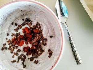Colazione sana nutriente senza zucchero senza glutine e senza uova: yogurt Bowl con Acai in polvere granella di cacao cruda e bacche di Goji